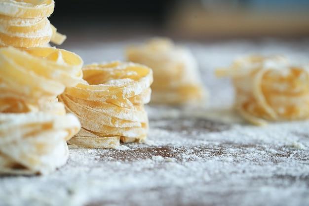 Cuisson des pâtes italiennes maison sur fond sombre