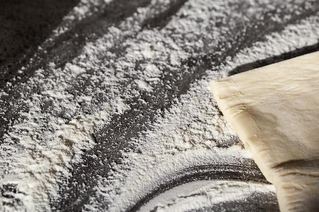Cuisson à plat poser sur la table la pâte, la farine sur fond gris. menu de cuisson, recette, concept de pâtisserie maison. vue de dessus avec espace de copie pour votre texte.