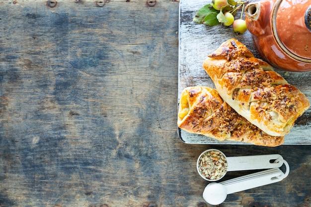 Cuisson à la pomme, pommes fraîchement cuites au four et brioches à la cannelle faites de pâte feuilletée sur une table en bois blanc. vue de dessus, style rustique, espace copie.