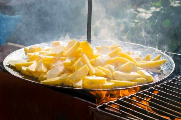 Cuisson de pommes de terre frites à la française pour le pique-nique au barbecue. pommes de terre frites