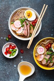 Cuisson des ramen de soupe de nouilles japonaises. ramen au porc tranché, narutomaki, œuf et cuillère de cuisine avec bouillon sur fond de pierre rustique. faire un plat traditionnel du japon, vue de dessus, gros plan, concept
