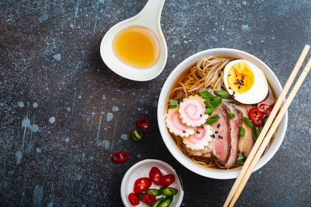 Cuisson des ramen de soupe de nouilles japonaises. ramen au porc tranché, narutomaki, œuf, cuillère de cuisine avec bouillon sur fond de pierre rustique. faire un plat traditionnel du japon, vue de dessus, gros plan. espace pour le texte