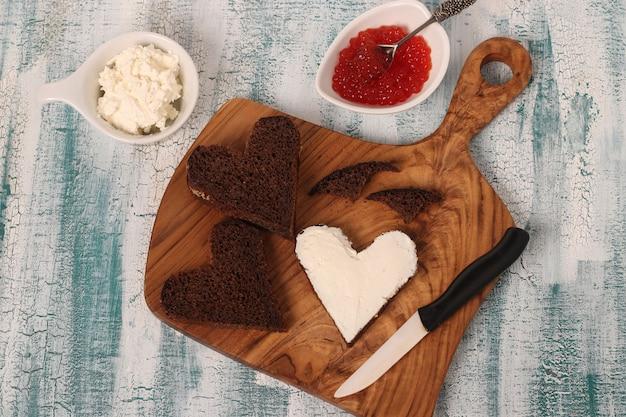 Cuisson des sandwichs avec du caviar rouge et du fromage à la crème en forme de coeur pour la saint-valentin, vue de dessus
