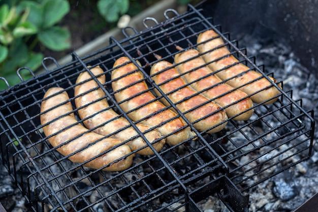 Cuisson des saucisses bavaroises sur un barbecue à l'extérieur. pique-nique, manger à l'extérieur.
