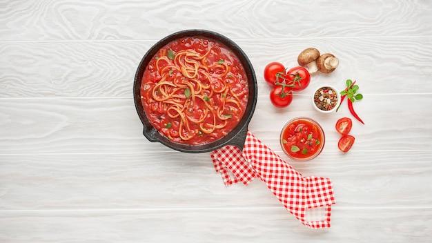 Cuisson des spaghettis avec sauce tomate bouillie dans une poêle en fonte servie avec piment, basilic frais, tomates cerises et épices sur table en bois de texture blanche, ingrédients food concept
