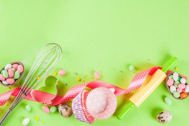 Cuisson sucrée pour pâques, cuisson avec cuisson au rouleau à pâtisserie, fouet pour fouetter, emporte-pièces, saupoudrage de sucre, farine. fond vert clair, vue de dessus
