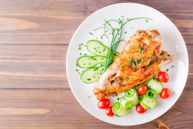 Cuit dans une aile de dinde aux épices, des tranches de concombre et des tomates cerises sur une plaque sur une table en bois. vue de dessus