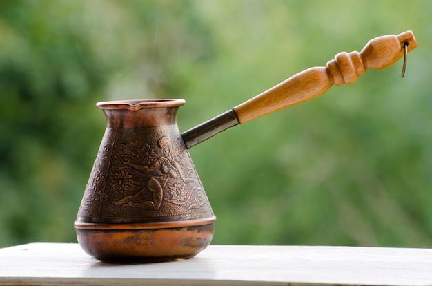 Cuivre cezve avec café chaud sur un rebord de fenêtre, fond vert flou