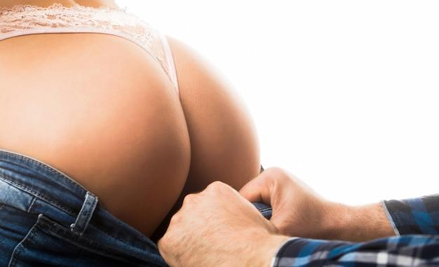 Cul féminin en string de sous-vêtements fille sexy main masculine touchant une fille sexy femme en sous-vêtements
