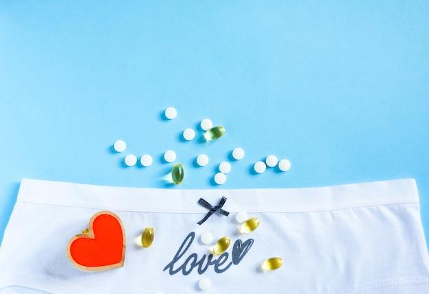 Culotte blanche féminine avec arc et mot grandi amour, coeur et pilules sur bleu