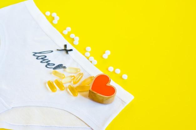 Culotte blanche féminine avec arc et mot grandi amour, coeur et pilules sur jaune