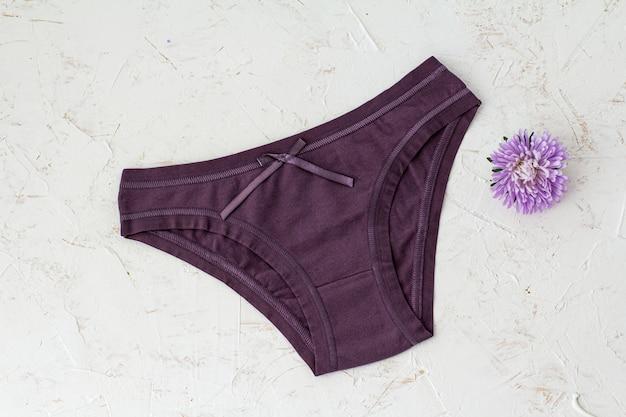 Culotte violette en coton avec bouton floral sur fond blanc structuré. ensemble de sous-vêtements femme. vue de dessus.