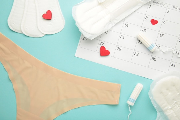 Culottes pour femmes avec serviettes et tampons menstruels sur fond bleu. vue de dessus. concept de jours critiques, menstruation, hygiène féminine. vue de dessus