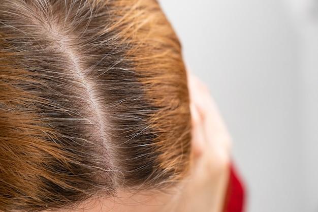 Cultivé après avoir coloré les racines grises des cheveux sur la tête d'une femme