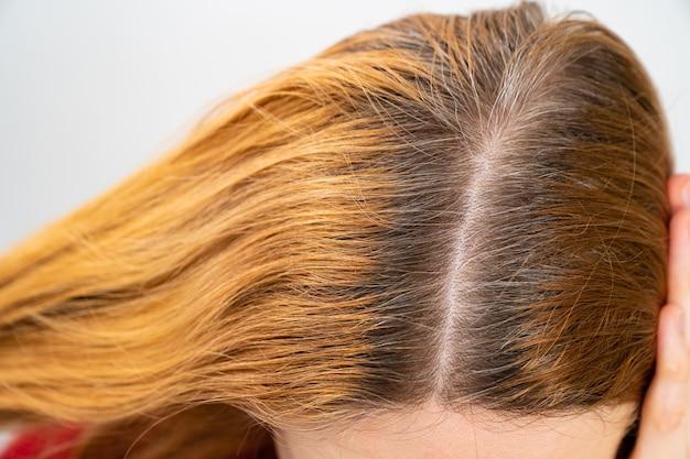 Cultivé après avoir taché les racines grises des cheveux sur la tête d'une femme. salon de beauté et coiffeur.