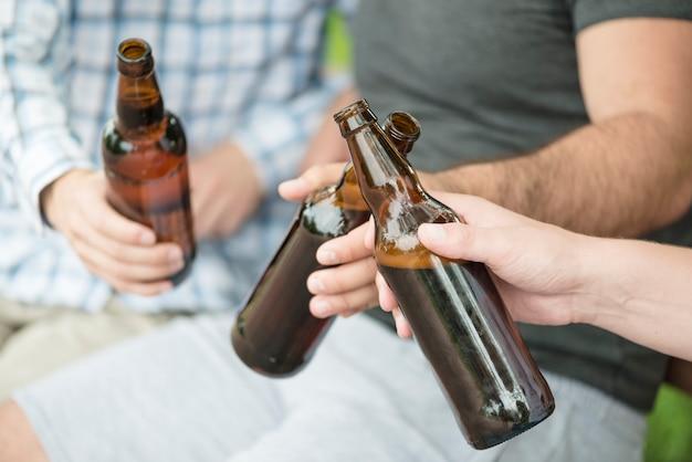 Culture des hommes clink bouteilles sur le banc