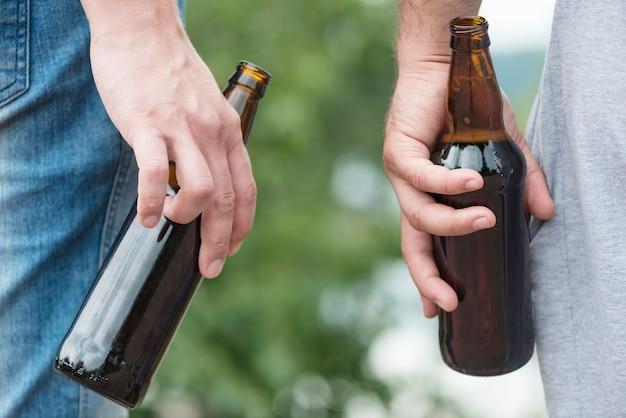 Culture des hommes relaxants avec de la bière dans la nature