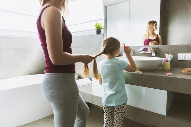 Culture mère tressage fille dans la salle de bain