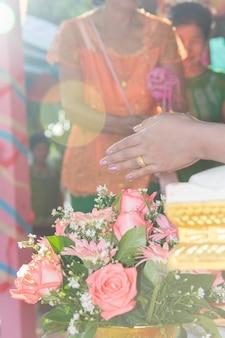Culture thaïlandaise, main d'une épouse recevant de l'eau bénite lors d'une cérémonie de mariage
