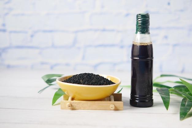 Cumin noir dans un bol avec de l'huile dans un bocal sur table