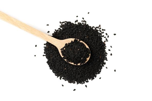 Cumin noir ou graines épicées de carvi noir dans une cuillère en bois isolé. nigella sativa également connu sous le nom de nigella, kalojeere et kalonji vue de dessus