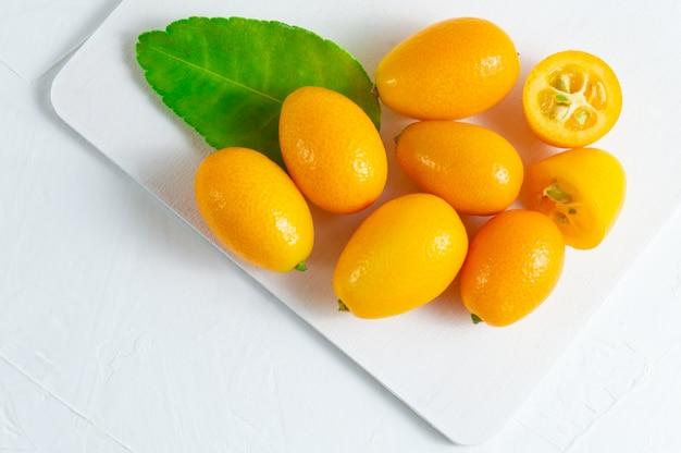 Cumquat ou kumquat avec une feuille verte sur un fond en bois blanc.