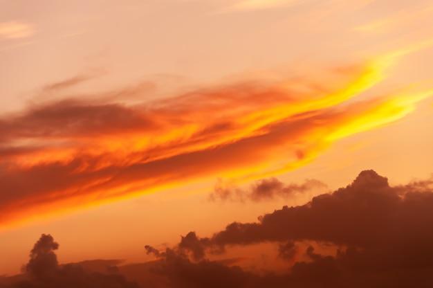 Cumulonimbus orange et jaune en formation diagonale éclairée par la lumière du coucher du soleil.