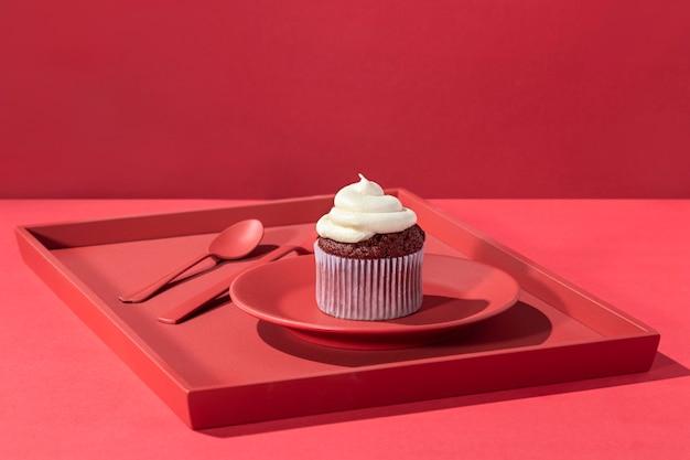 Cupcake à angle élevé avec de la crème sur une assiette
