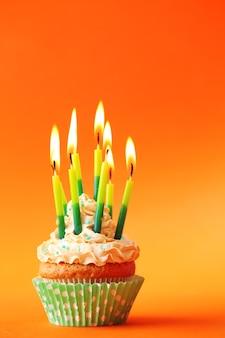 Cupcake d'anniversaire avec des bougies sur la couleur