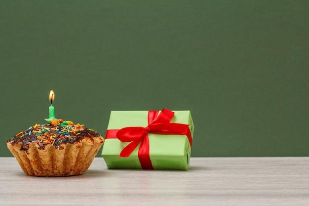 Cupcake d'anniversaire, décoré d'une bougie festive brûlante et d'une boîte-cadeau sur fond vert. concept minimal de joyeux anniversaire.