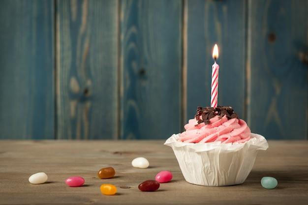 Cupcake d'anniversaire fait maison avec bougie et bonbons colorés