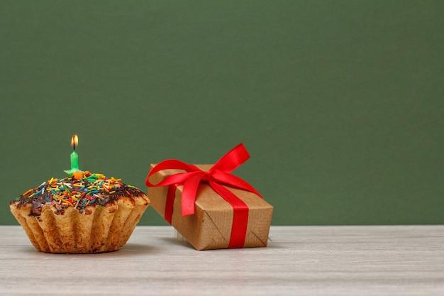 Cupcake d'anniversaire avec glaçage au chocolat, décoré d'une bougie festive allumée et d'une boîte-cadeau avec ruban rouge sur fond vert. concept minimal de joyeux anniversaire.