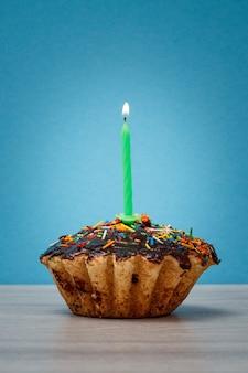 Cupcake d'anniversaire savoureux avec glaçage au chocolat et caramel, décoré d'une bougie festive allumée sur fond bleu. concept minimal de joyeux anniversaire.