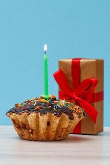 Cupcake d'anniversaire savoureux avec glaçage au chocolat et caramel, décoré d'une bougie festive brûlante et d'une boîte-cadeau sur fond bleu. concept minimal de joyeux anniversaire.