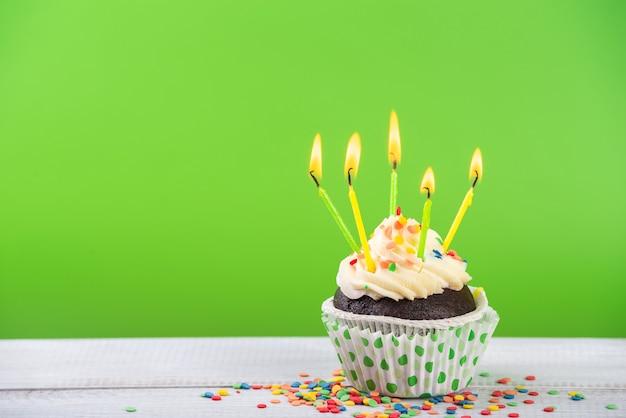 Cupcake d'anniversaire sur vert avec des bougies multicolores.
