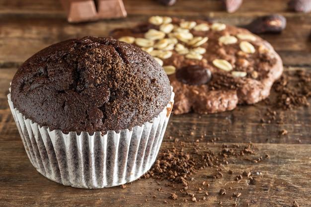 Cupcake au chocolat et cracker aux pépites d'amandes et sur bois avec ton sombre