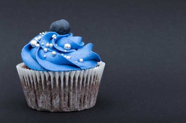 Cupcake aux bleuets sur une surface noire