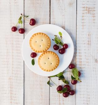 Cupcake aux cerises sur des planches en bois blanches