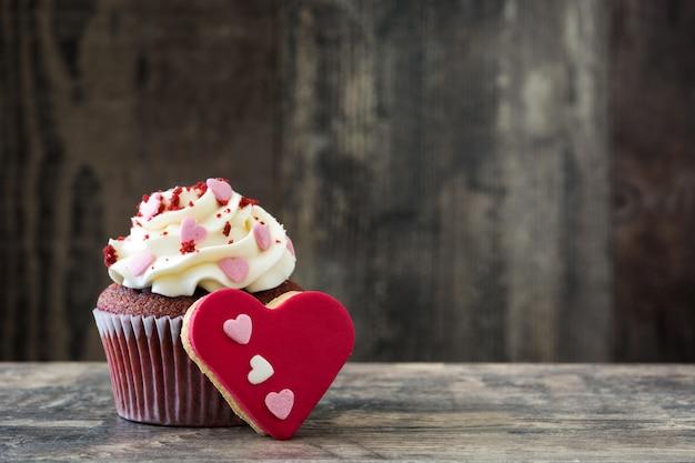 Cupcake et biscuit de la saint-valentin en forme de cœur décoré de coeurs sucrés sur table en bois
