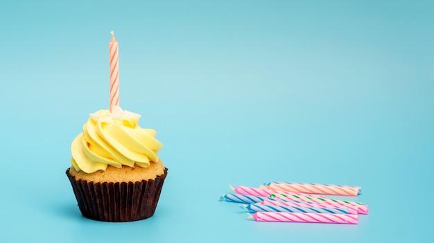Cupcake et bougie sur un fond bleu.