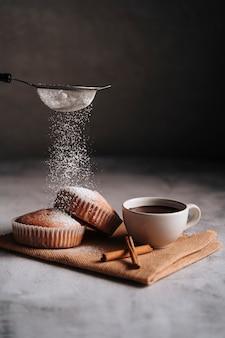 Cupcake sur un chiffon en fibre avec un chocolat chaud dans une tasse et quelques morceaux de cannelle.