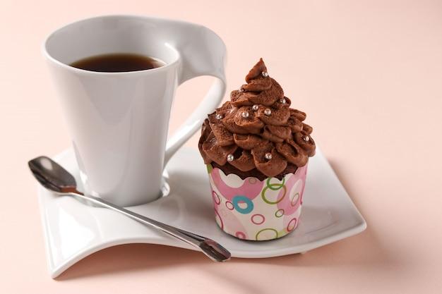 Cupcake à la crème au chocolat et une tasse de café disposés sur un rose