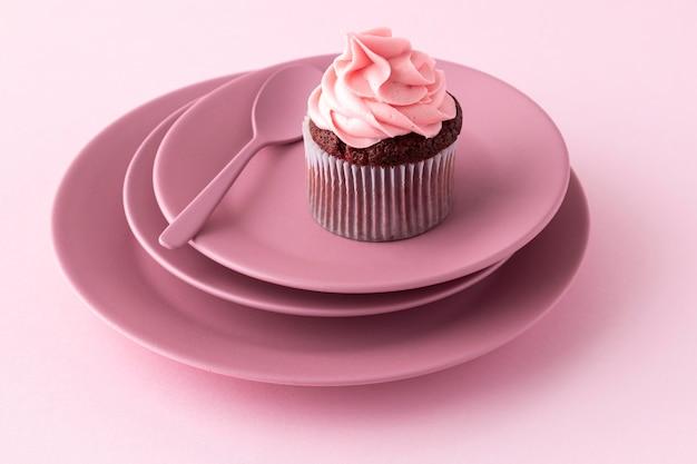 Cupcake et cuillère à angle élevé sur des assiettes