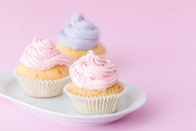 Cupcake décoré de crème au beurre rose et violet sur fond rose pastel.