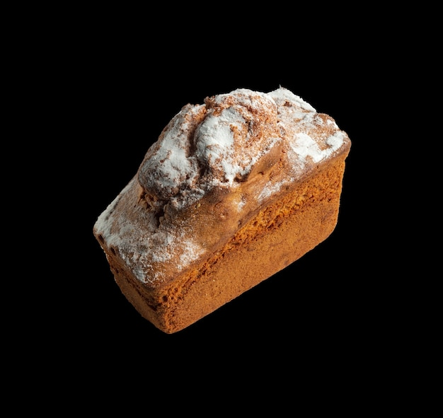 Cupcake fait maison entier saupoudré de sucre en poudre sur fond noir isolé plat national