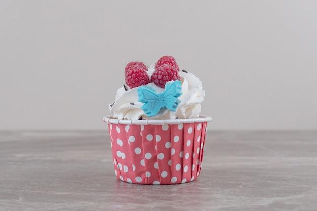 Un cupcake garni de crème et de fruits rouges sur marbre