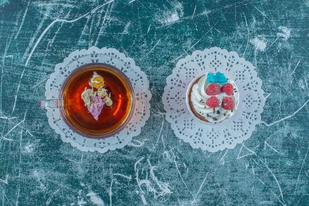 Cupcake garni de crème et une tasse de thé sur fond bleu. photo de haute qualité