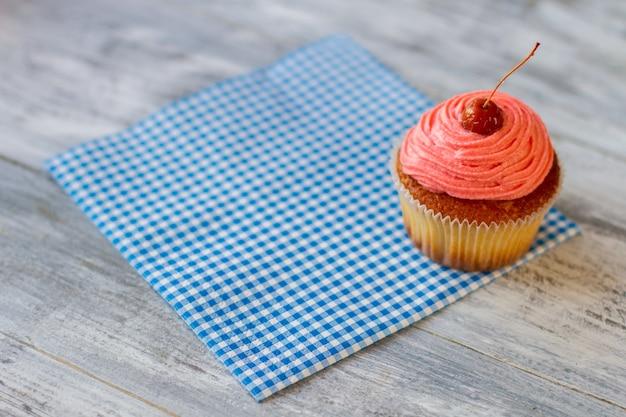 Cupcake givré sur une serviette dessert avec une cerise sur le dessus de la pâtisserie servi au café régal sucré pour vis ...