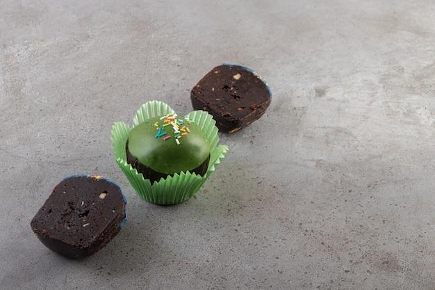 Cupcake glacé vert avec des paillettes placés sur une table beige.