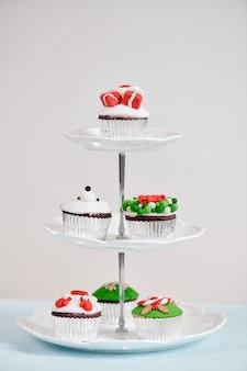 Cupcake de noël fait maison avec des éléments de symboles décoratifs verts rouges traditionnels